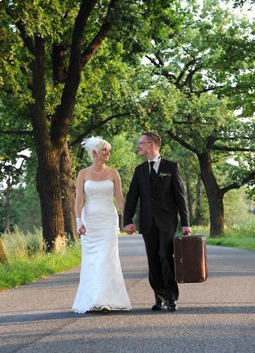 Hochzeitspaar mit Reisekoffer läuft auf Landstraße
